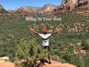 Man facing red rock scene in Sedona, with this arms outstretched.